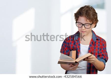 cute elementary school boy holding book - stock photo