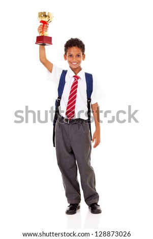 cute elementary schoolboy holding a trophy isolated on white