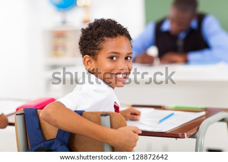 cute elementary schoolboy looking back in classroom