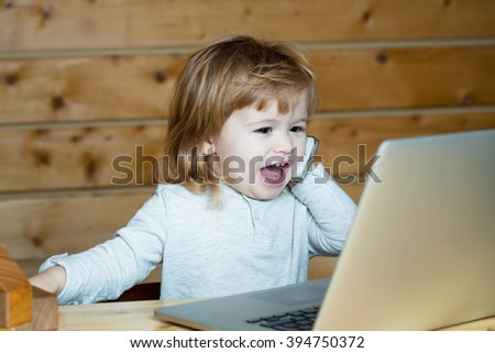 Cute emotional funny little baby boy with long blonde curly hair speaking by mobile phone near computer indoor on wooden background, horizontal picture - stock photo