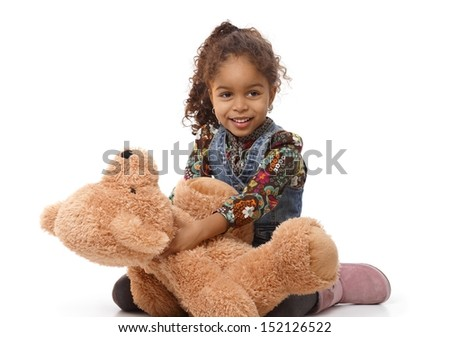 Cute ethnic little girl holding huge plush bear, playing, smiling.