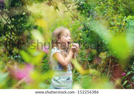 Cute european blond girl ready to eat green apple in summer blooming park