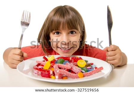 cute European female child smiling happy eating candy with spoon fork and knife in sugar abuse , unhealthy sweet nutrition concept , children candy addiction and kids  dental care - stock photo