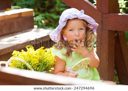 Cute european toddler girl in colorful clothes and hat sitting outdoors with flowers and round candy with toe in mouth - stock photo
