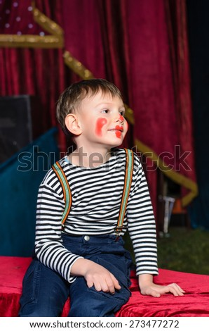 Cute excited little boy in comic red makeup sitting on a plush seat grinning happily at the camera as he prepares for a pantomime - stock photo