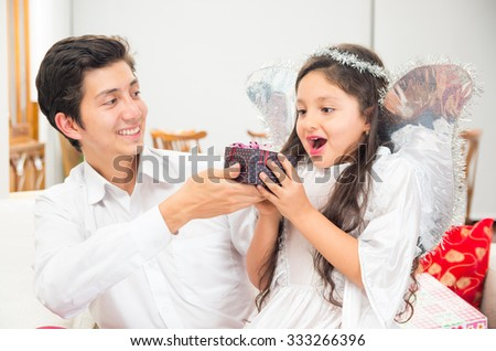 Cute excited little girl dressed as Christmas angel receiving present from dad