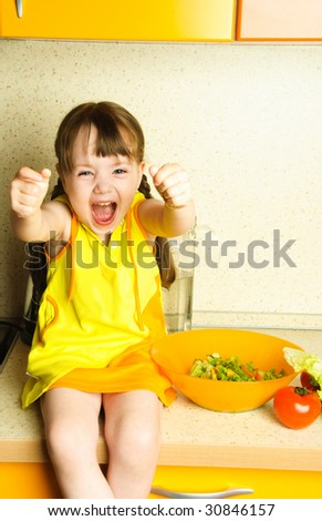 cute excited little girl making salad in the kitchen - stock photo