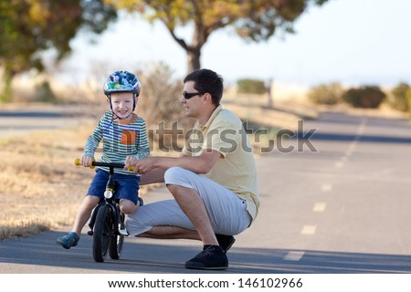 cute excited son at balance bike and his handsome father having fun time together outside - stock photo