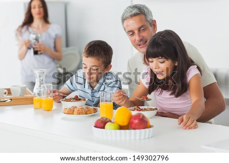 Cute family eating breakfast in kitchen together at home - stock photo