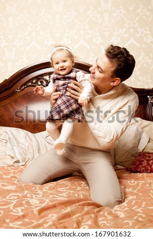 Cute family in the bedroom. Father and daughter in the interior. Dad and baby are playing together. - stock photo