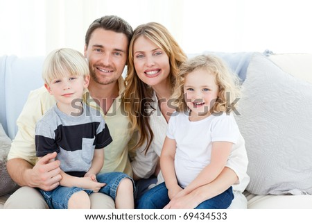 Cute family in their sofa at home - stock photo