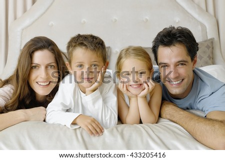 Cute family lying on bed in the morning - stock photo