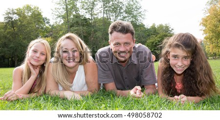 Cute family lying on grass in park with two girls