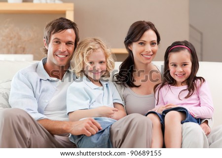 Cute family watching television together in a living room - stock photo