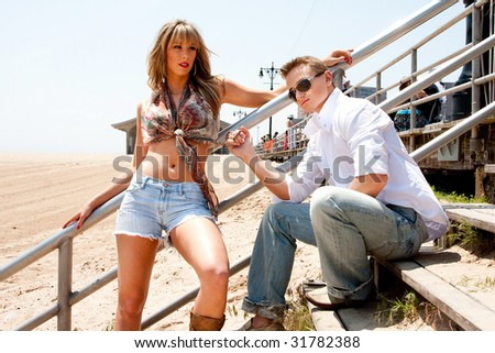 Cute fashion couple; sexy female and handsome guy sitting on stairs next to boardwalk on the beach on a sunny summer day