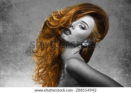 cute fashion portrait in black and white with part in color , HDR effect, of sexy female in sensual pose with naked shoulders and creative bushy hair-style   - stock photo