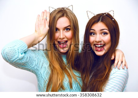 Cute fashion portrait of pretty sisters girls having fun together hugs and going crazy, funny cat ears, mint winter sweaters, white wall, best friends, joy, trend, relations, happy, natural make up. - stock photo