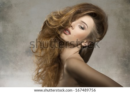 cute fashion portrait of sexy female in sensual pose with naked shoulders and creative bushy hair-style   - stock photo