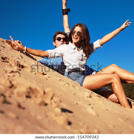Cute fashion young beautiful couple having fun and put hands up in the air in summer on the beach.  - stock photo