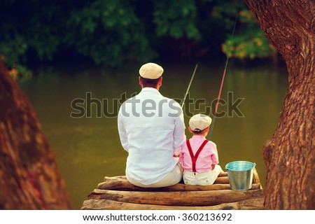 cute father and son fishing together among beautiful pristine nature - stock photo