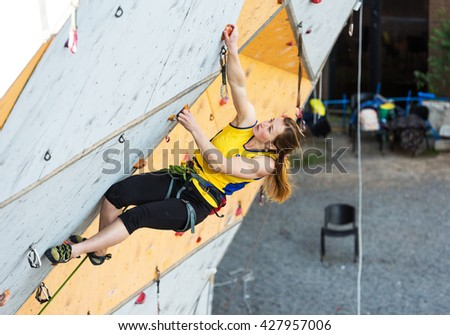 Cute female Athlete hanging on climbing Wall making hard move. National Climbing competitions, Dnipro, Ukraine, May 20, 2016 - stock photo