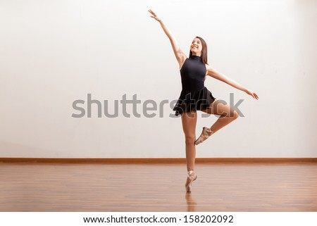 Cute female ballet dancer standing on the tip of her toes and smiling in a studio - stock photo