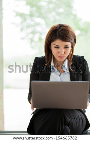 Cute female business school student sitting on a bench and working on a laptop computer - stock photo