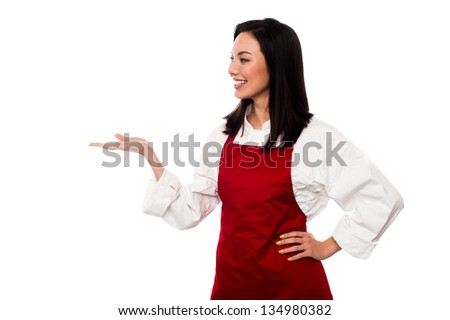 Cute female chef promoting bakery product. Copy space concept. - stock photo