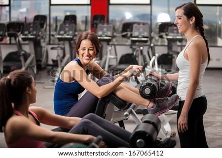 Cute female friends chatting and hanging out in a gym while exercising - stock photo