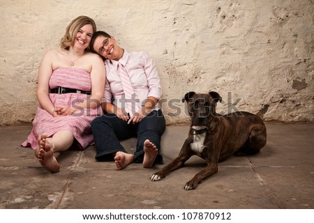 Cute female friends with pet dog in basement - stock photo