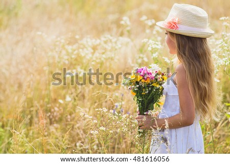 Cute female kid with flowers on meadow