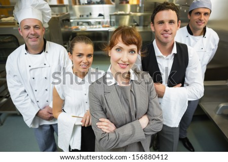 Cute female manager posing with the staff in a modern kitchen - stock photo