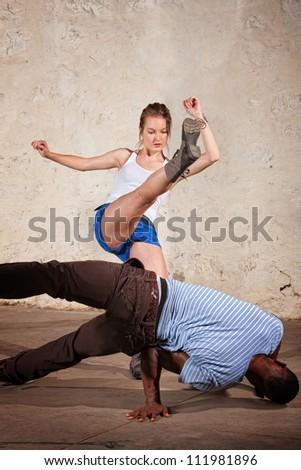 Cute female martial artist performs a Capoeria crescent kick - stock photo