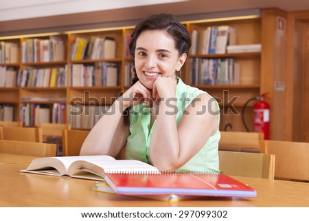 Cute female student studying at the university library - stock photo