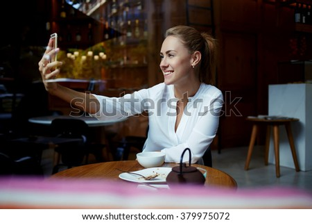 Cute female student with beautiful smile making photo on mobile phone while sitting in modern coffee shop, happy woman photographing herself via cell telephone camera during lunch in comfortable cafe  - stock photo