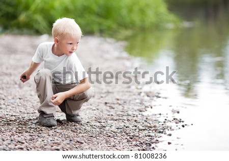 cute five year old boy throwing stones to the water outdoor on a summer day - stock photo