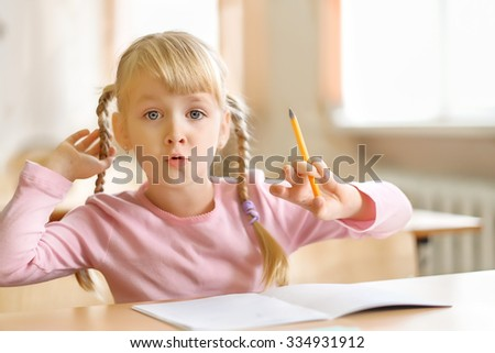 Cute five years old  blonde girl sitting at classroom and writing