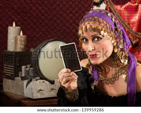 Cute fortune teller in ornate dress with tarot card - stock photo