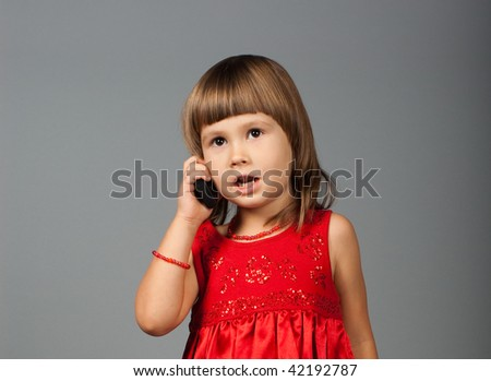 Cute four-year-old girl in red dress talking on the phone