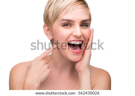 Cute fun laughing female with perfect white teeth straight smile pointing at mouth - stock photo