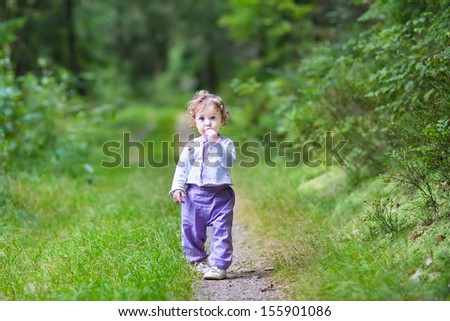 Cute funny baby girl walking in a beautiful autumn pine forest