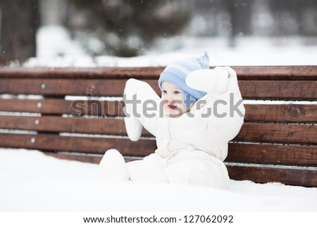 Cute funny baby sitting on a bench in a park on a snowy winter day - stock photo