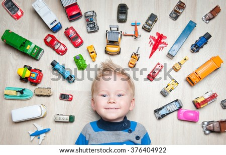 Cute funny Boy with toy cars around him - stock photo