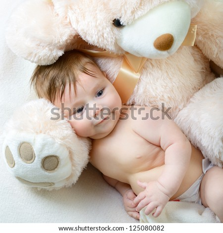 cute funny infant baby boy with big toy bear, beautiful kid's portrait closeup - stock photo