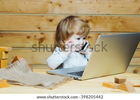 Cute funny little baby boy with long blonde curly hair playing on computer and mobile phone near toy building blocks indoor on wooden background, horizontal picture - stock photo