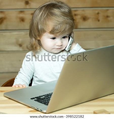 Cute funny little baby boy with long blonde curly hair speaking by mobile phone near computer indoor on wooden background, square picture - stock photo