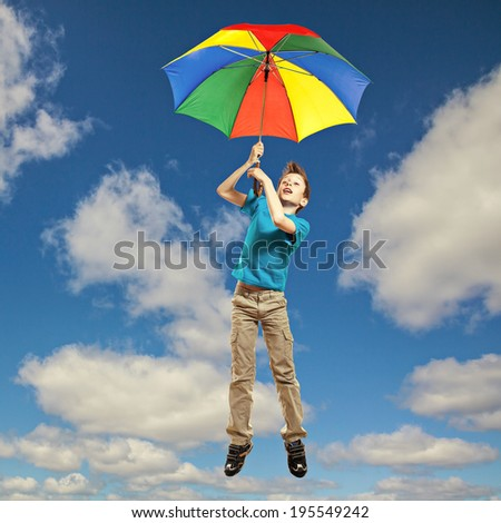 Cute funny little child in t-shirt flying in the sky with a colorful umbrella
