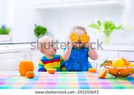 Cute funny little girl and adorable baby boy drinking freshly squeezed orange juice for healthy breakfast in a white kitchen with window on a sunny summer morning - stock photo