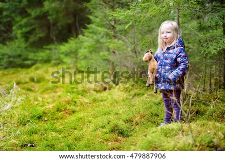 Cute funny little girl having fun during hike in a woods on beautiful spring day