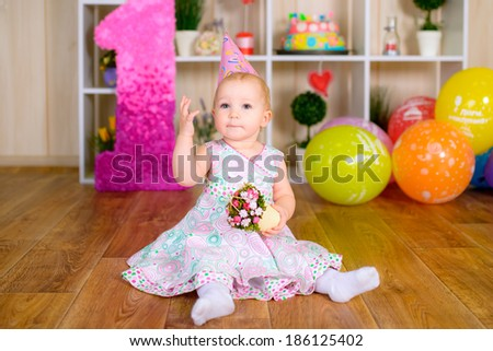 Cute funny little girl in first birthday with colored balloons